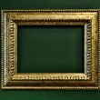 Gold empty picture frame border on green wall — Stock Photo