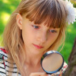 Young girl with magnifying glass in the park — Stock Photo #6855539