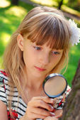 Young girl with magnifying glass in the park — Stock Photo