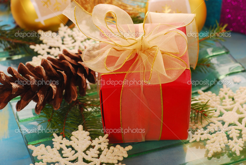 Little red gift box with  golden ribbon in christmas decoration  — Stock Photo #6855639
