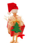 Wooden mannequin holding christmas gift box — Stock Photo
