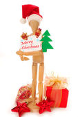 Wooden mannequin holding christmas card — Stock Photo