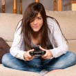 Young female playing video-games concentrating on sofa at home — Stock Photo #7568815