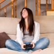 Young female lose playing video-games concentrating on sofa at home — Stock Photo #7568875