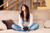 Young female lose playing video-games concentrating on sofa at home — Stockfoto