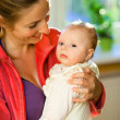 Foto Stock: Mother holding beautiful baby girl