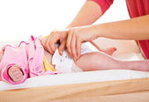 Mother changing little girl's diaper on nursery table — Stok fotoğraf