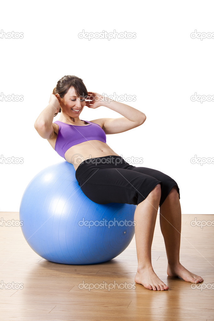 Beautiful young and athletic woman making exercises on a fitness ball  Stock Photo #7869133