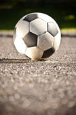 Soccer ball on asphalt — Stock Photo