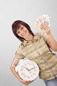 женщина холдинг часы и деньги — Стоковое фото