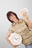 Woman holding clock and money — Stock Photo