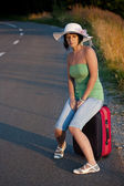Woman sitting on a suitcase — Stockfoto