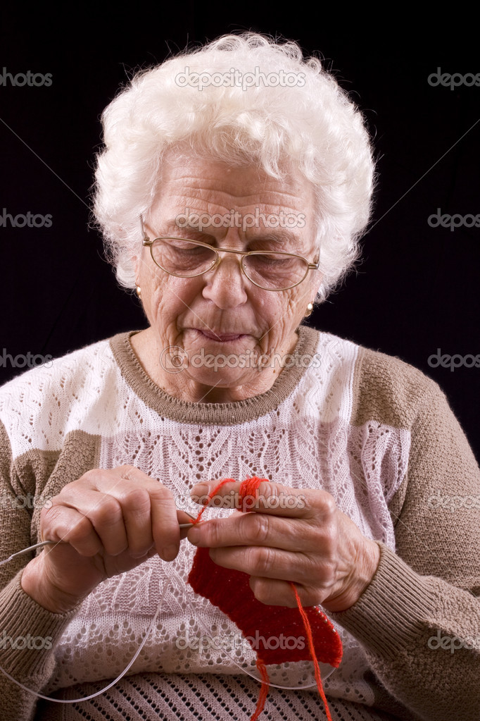 Portrait of grandmother knitting isolated in black — Stock Photo #6871463