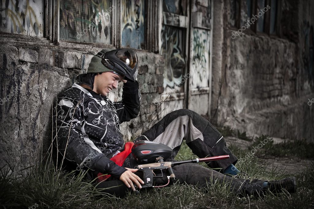 Paintball player relaxing with marker in grunge background — Stock Photo #6871530