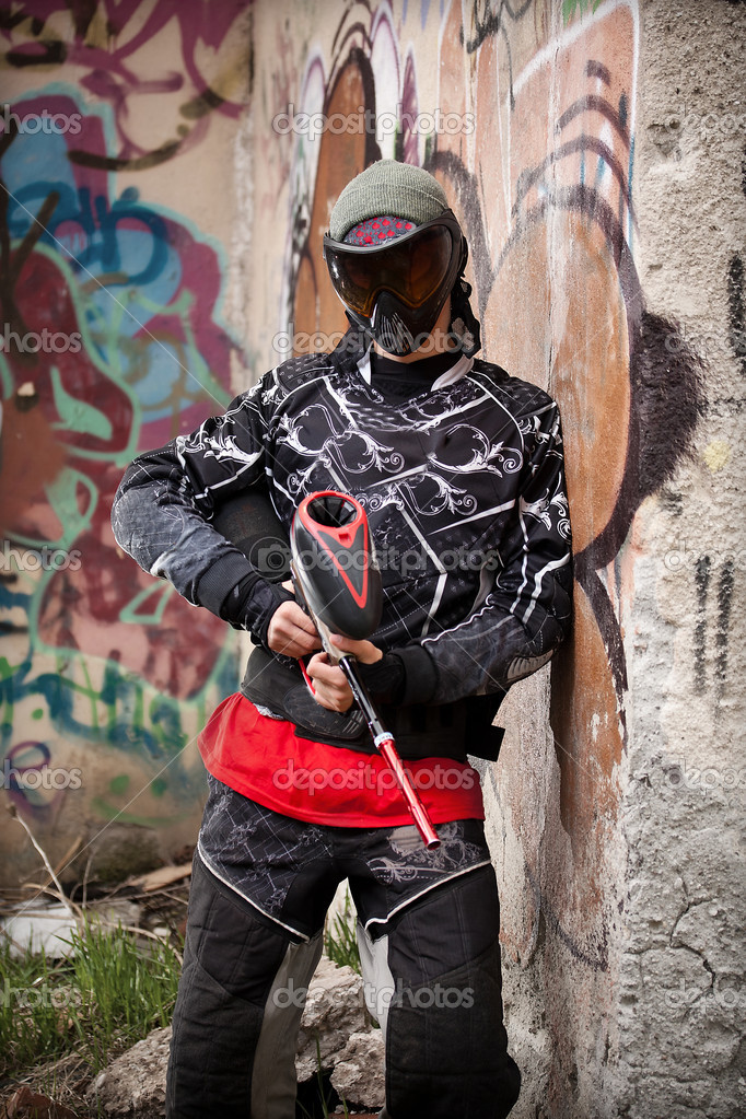Paintball player relaxing with marker in grunge background — Stock Photo #6871558