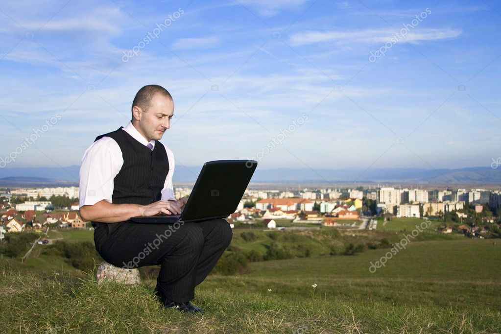 Freedom - Man working with laptop city in background  Stock Photo #6871762