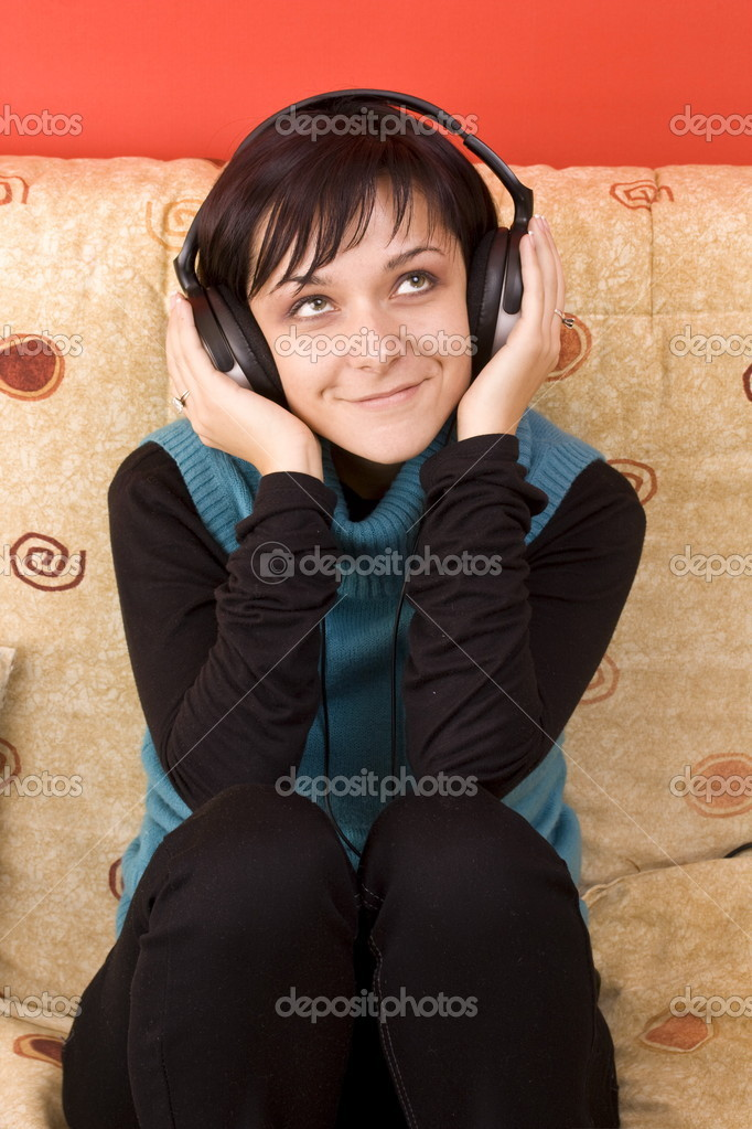 Happy woman with headphones lying down on sofa in lounge, listen to music   Stock Photo #6872330