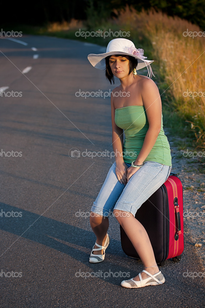 Beautiful woman sitting on a suitcase by a countryside road  — Lizenzfreies Foto #6872565