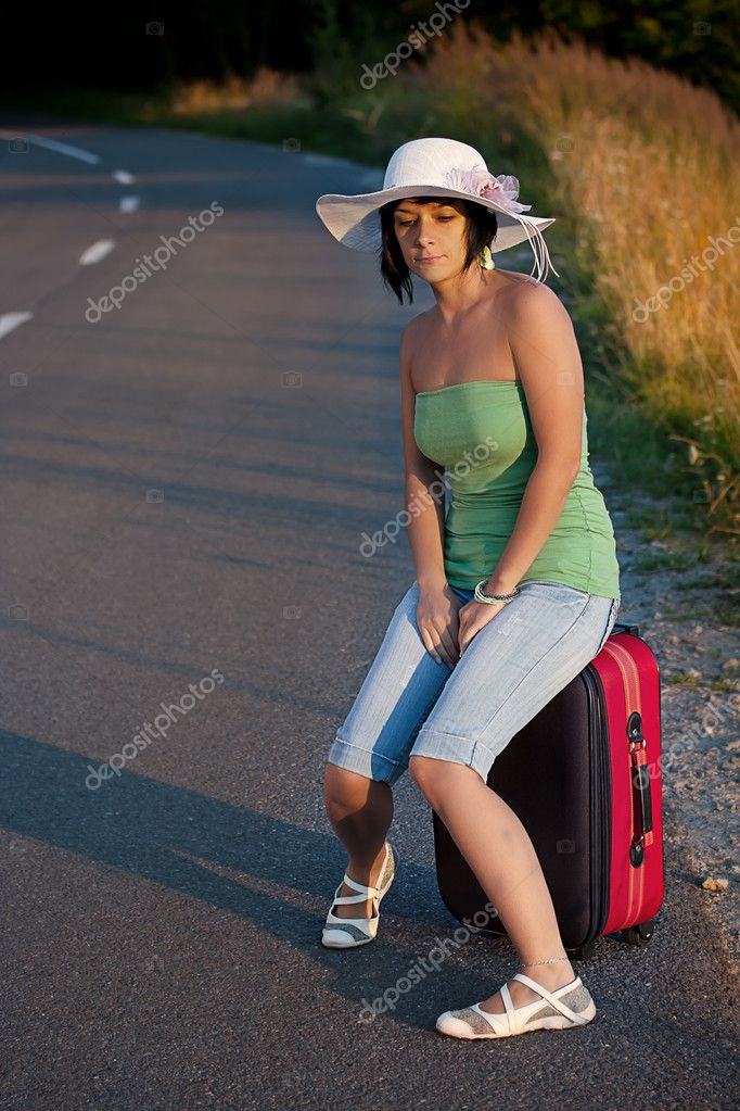 Beautiful woman sitting on a suitcase by a countryside road  — 图库照片 #6872565