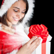 Stock Photo: Miss Santa opening a gift box