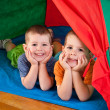 Foto Stock: Little boys lying inside colorful tent