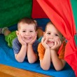 图库照片: Little boys lying inside colorful tent