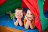Malí kluci ležící uvnitř barevný stan — Stock fotografie