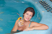 Woman enjoying vitamin drinks in jacuzzi — Stock Photo