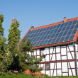 Old frame house with solar cells on roof — Stock Photo #7662273