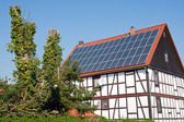 Old frame house with solar cells on the roof — Stock Photo
