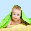 Adorable happy baby in colorful towel — Stock Photo