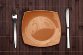 Bamboo placemat with square plate fork and knife — Stock Photo