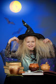 Girl dressed up as witch in night making magic — Stock Photo