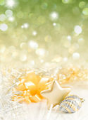 Gold and silver Christmas baubles on background of defocused gol — Stock Photo