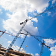 Construction cranes and unfinished house against the blue sky wi — Stockfoto