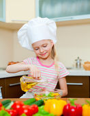 Little girl with oil preparing healthy food on kitchen — Stock Photo