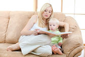 Son and mother sitting on sofa and reading book together — Stock Photo