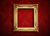Empty golden painting frame on vintage wallpaper — Stock Photo