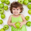 Adorable little girl lying with green apples — Stock Photo