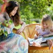 Girls reading book sitting in wicker chairs outdoor in summer da — Stock Photo
