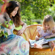 Girls reading book sitting in wicker chairs outdoor in summer da — Stock Photo #7511391