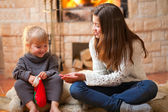 Two girls sitting fireside and opening christmas presents — Stock Photo