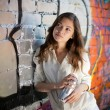 Stock Photo: Teenage girl portrait with spray cnear graffiti wall