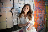 Teenage girl portrait with spray can near graffiti wall — Stock Photo