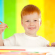 Red-haired adorable boy drawing with orange pencil on rainbow ba — Stock Photo