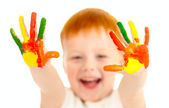 Adorable red-haired boy with focus on hands painted in bright co — Stock Photo