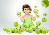 Adorable little girl sitting among falling green apples — Stock Photo