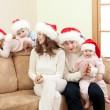 Happy family in Christmas Santa's hats on sofa in living room — Stock Photo