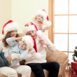 Happy family in Christmas Santa's hats on sofa in living room - Stock Photo