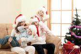 Happy family in Christmas Santa's hats on sofa in living room — Stock Photo